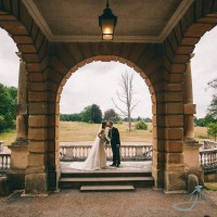 Clandon Park, bride & groom kiss under arch