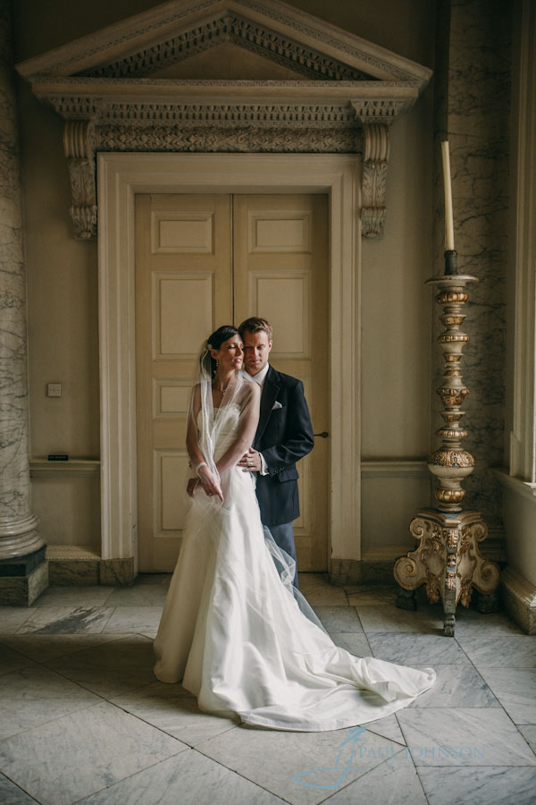 couple in contemporary pose in the main hall at Clandon Park