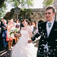 confetti being thrown over bride & groom as leaving the church