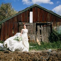 bride in front of derelict farm building near cooling castle