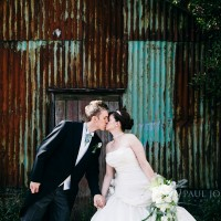 bride & groom kissing on wedding in front derelict farm building near cooling castle