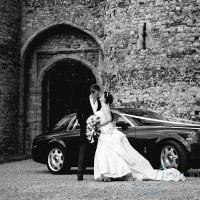 bride and groom in fron of cooling castle barn turrets