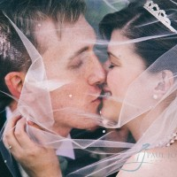 bride & groom close up kissing through veil