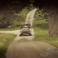 Vintage car drives up the drive of Wiston House, wedding venue in Sussex