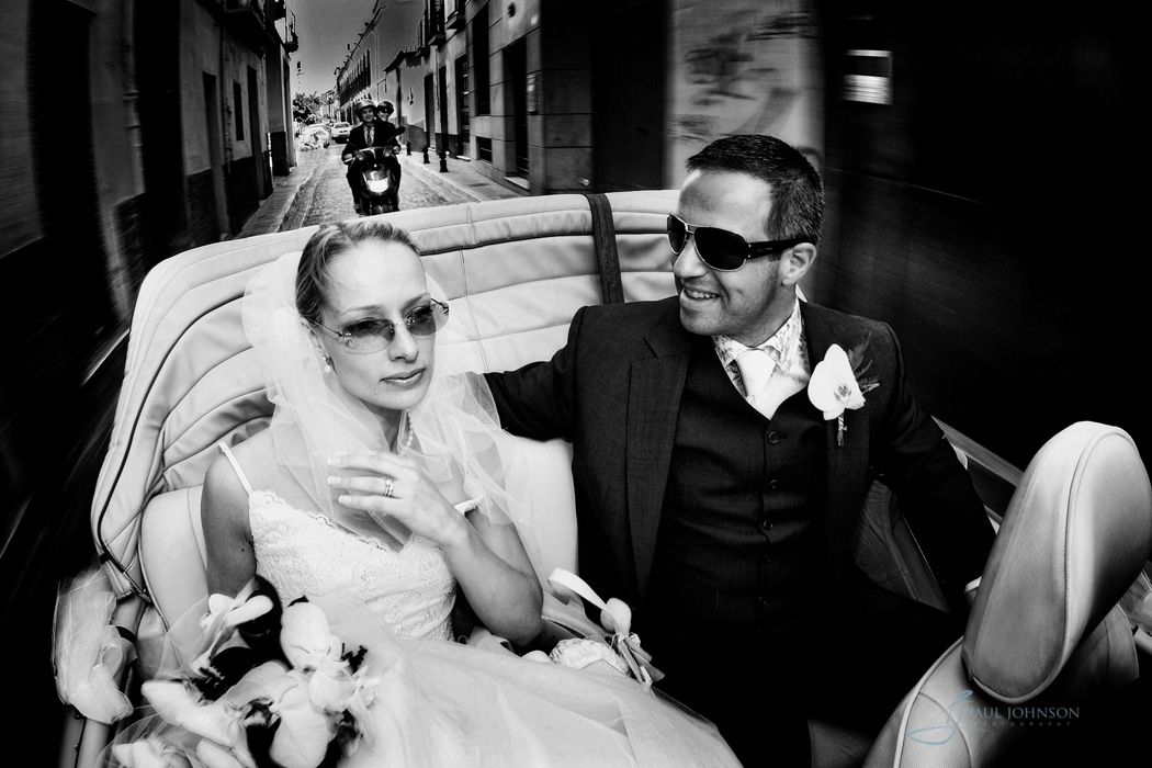 Bride and groom in open top car going to reception on the street of Granada, Spain