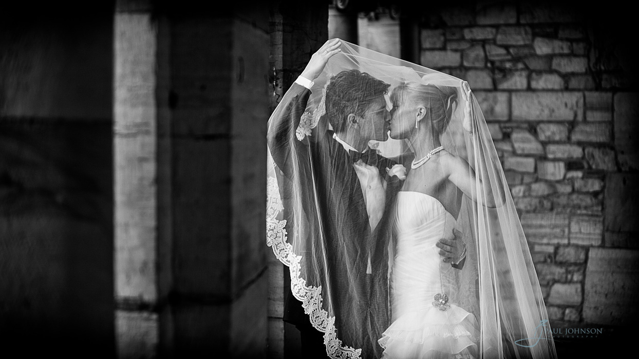 Bride and groom under the bride's veil in the grounds of Hever Castle, Kent