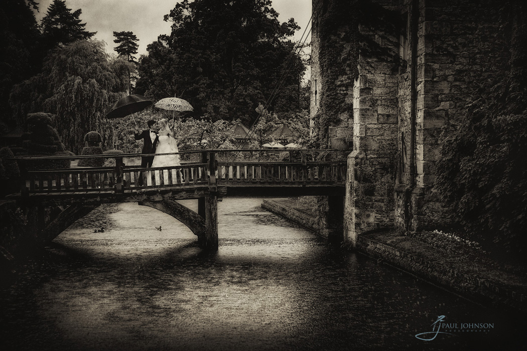 The draw bridge at Hever Castle, bride and groom in the rain