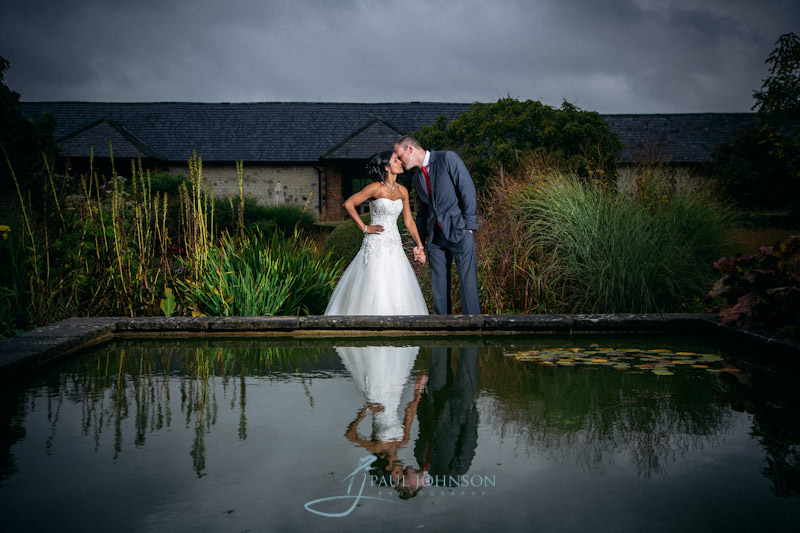 Bride & groom reflecion in th epond at Bury Court