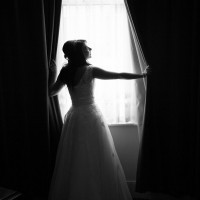 Bride looking through curtains