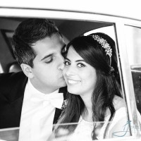 Groom kissing the bride inside wedding car
