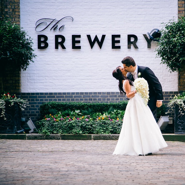 Bride & groom embrace with 'The Brewery' in the background